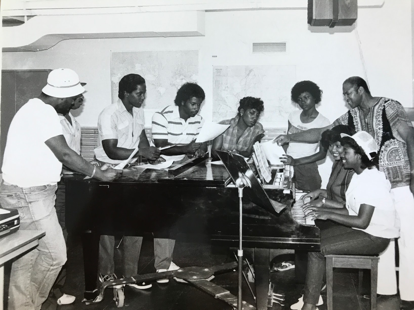 Historic photo of students singing at a piano