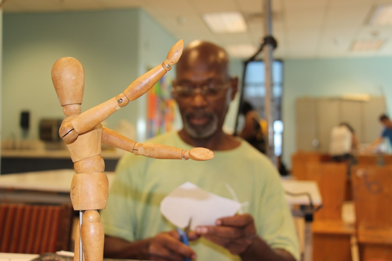 Student sitting in front of wooden mannequin
